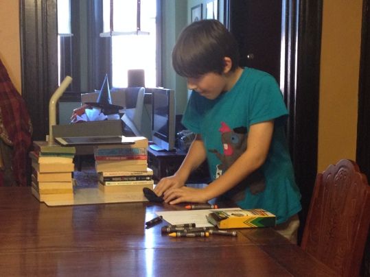 Mushroom working on our 90-Second Newbery Film. I set up the books so he could do the drawing and take the photos for the animation he's working on.